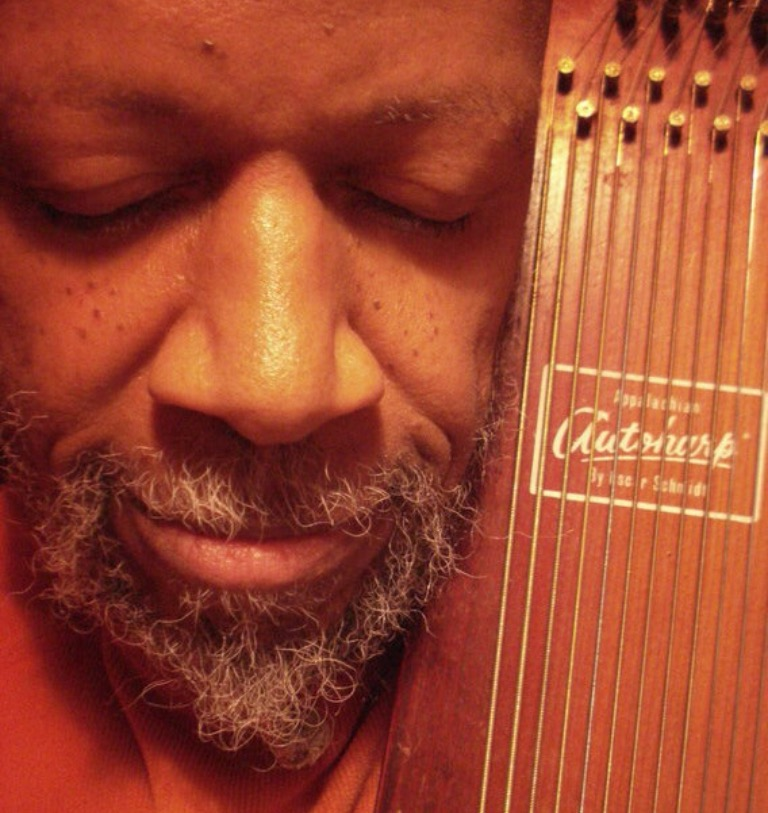 Laraaji with his eyes closed, holding his zither.