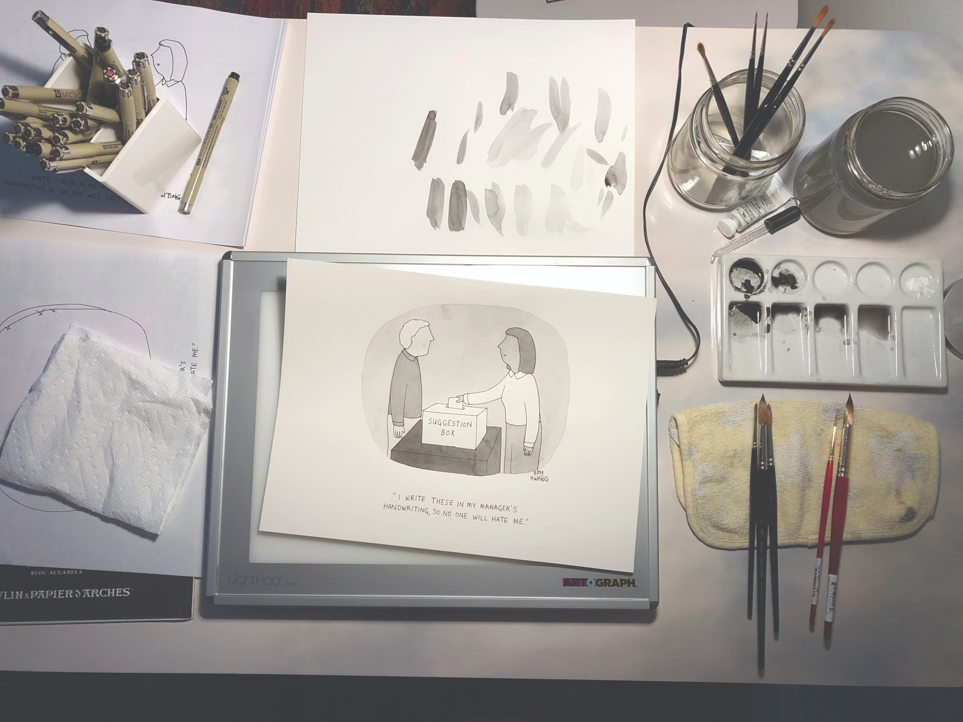Photo of Hwang's workspace, with an in-progress watercolor cartoon surrounded by watercolor materials