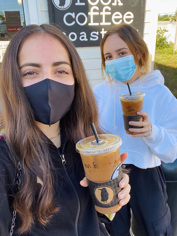 Two women holding iced coffees and wearing masks