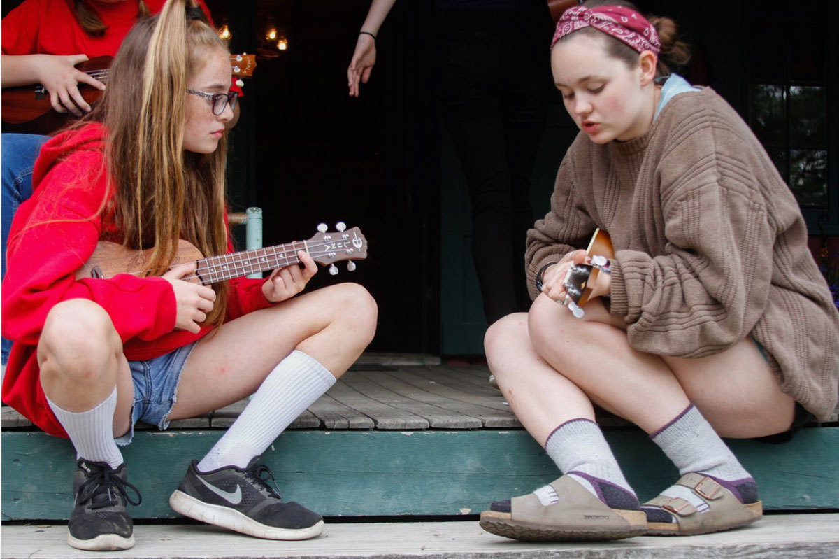 Ellie teaching student how to play the ukulele