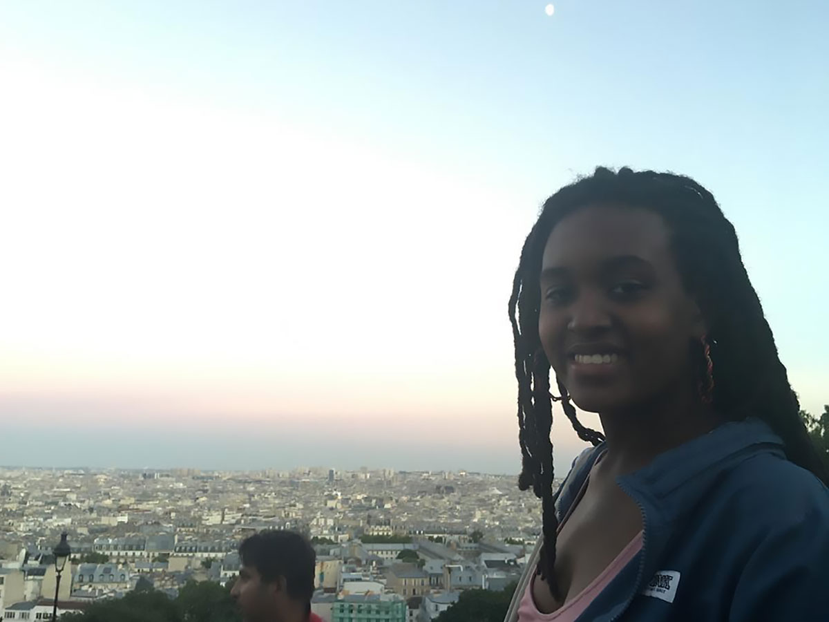 Young woman on a rooftop overlooking the city of Paris.