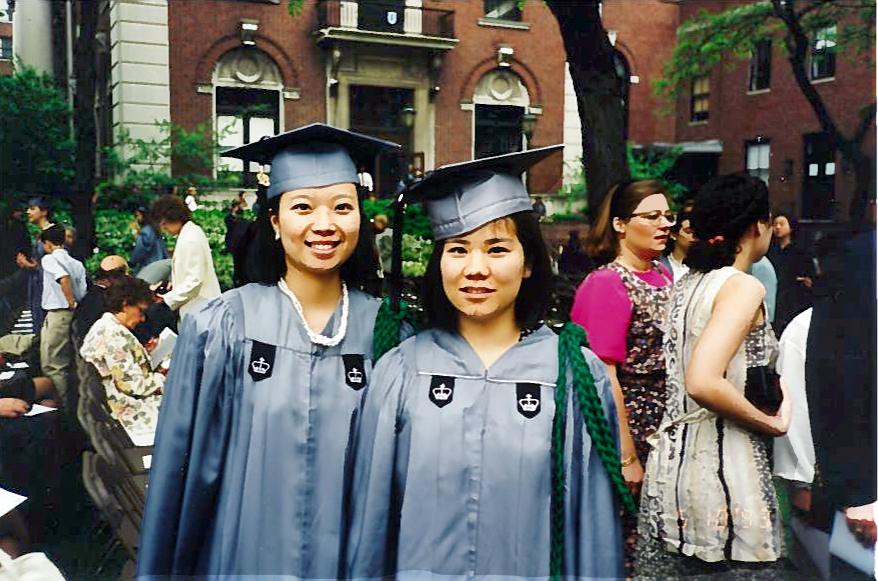 Two Asian American women dressed in Barnard regalia.