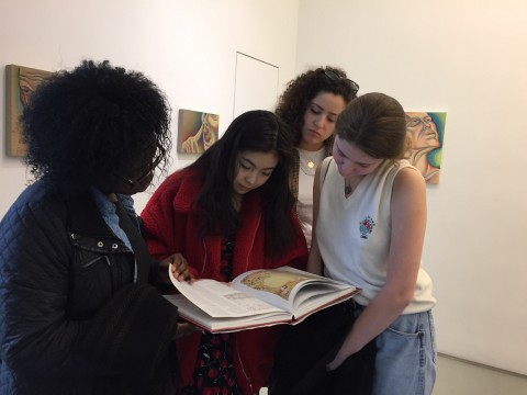 Scholars peruse a catalogue at the Judy Chicago exhibit PowerPlay
