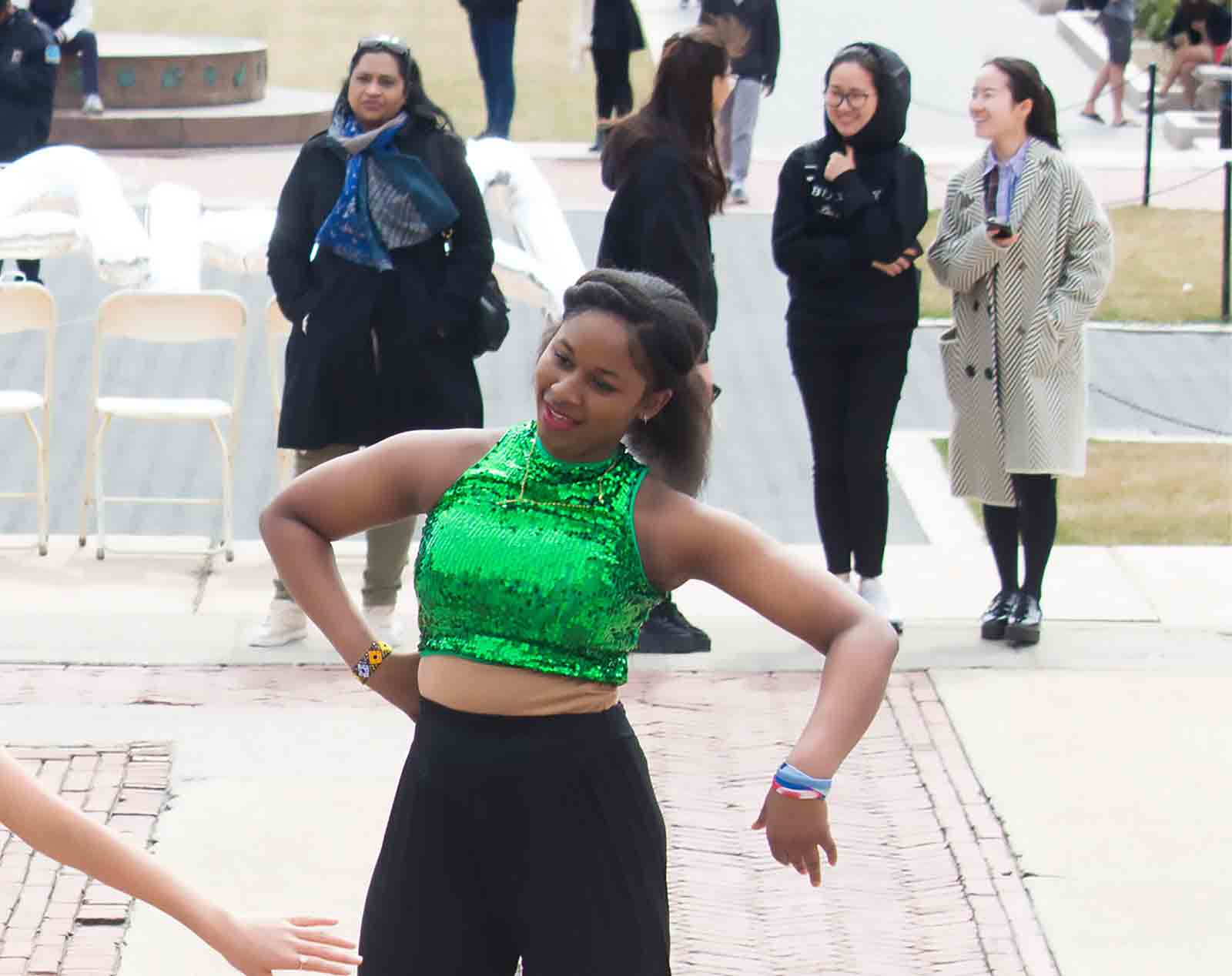 Young woman dancing wearing sequined green top