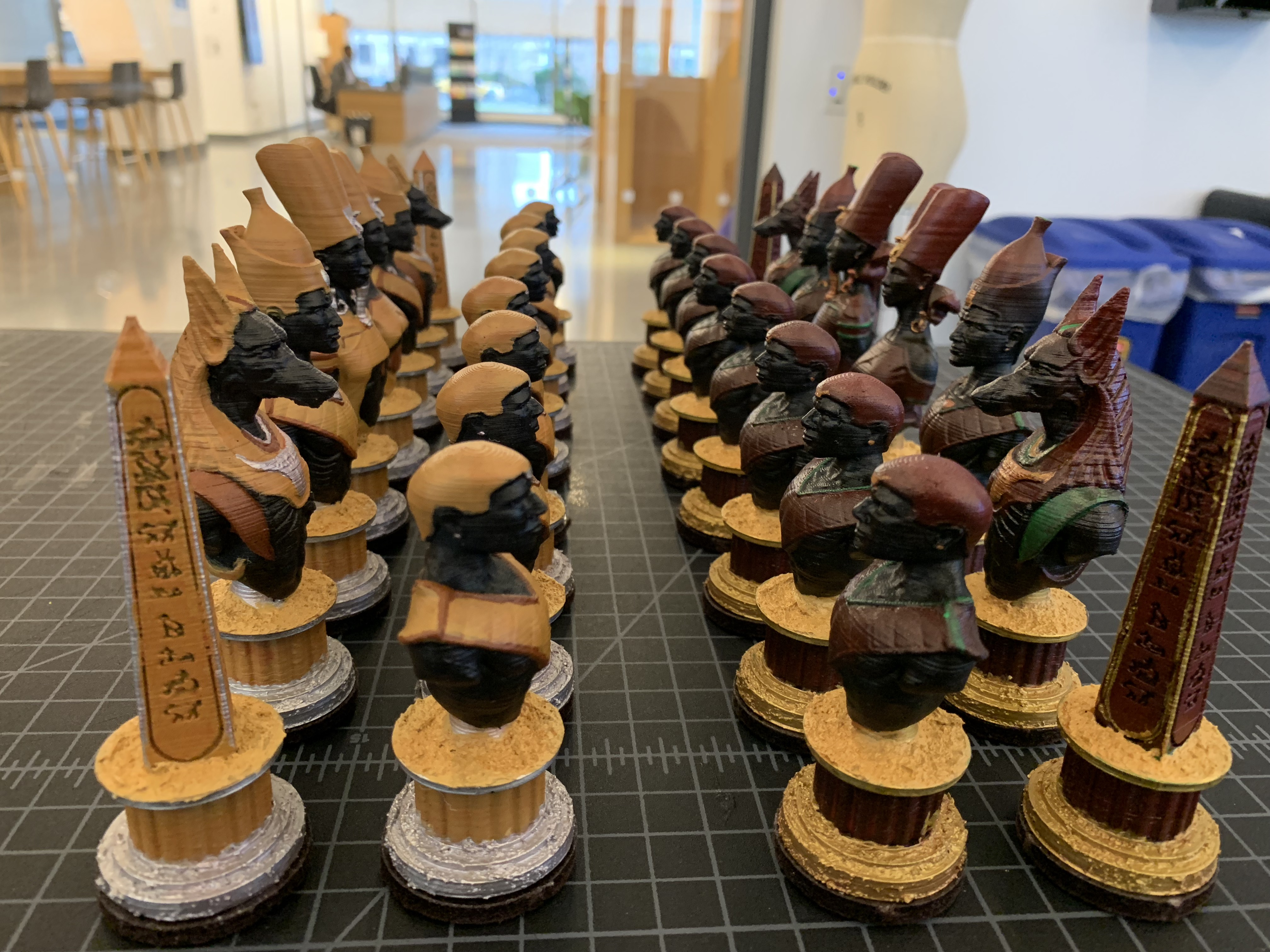 The completed chess pieces are arranged in four rows. The opposing sides face each other.