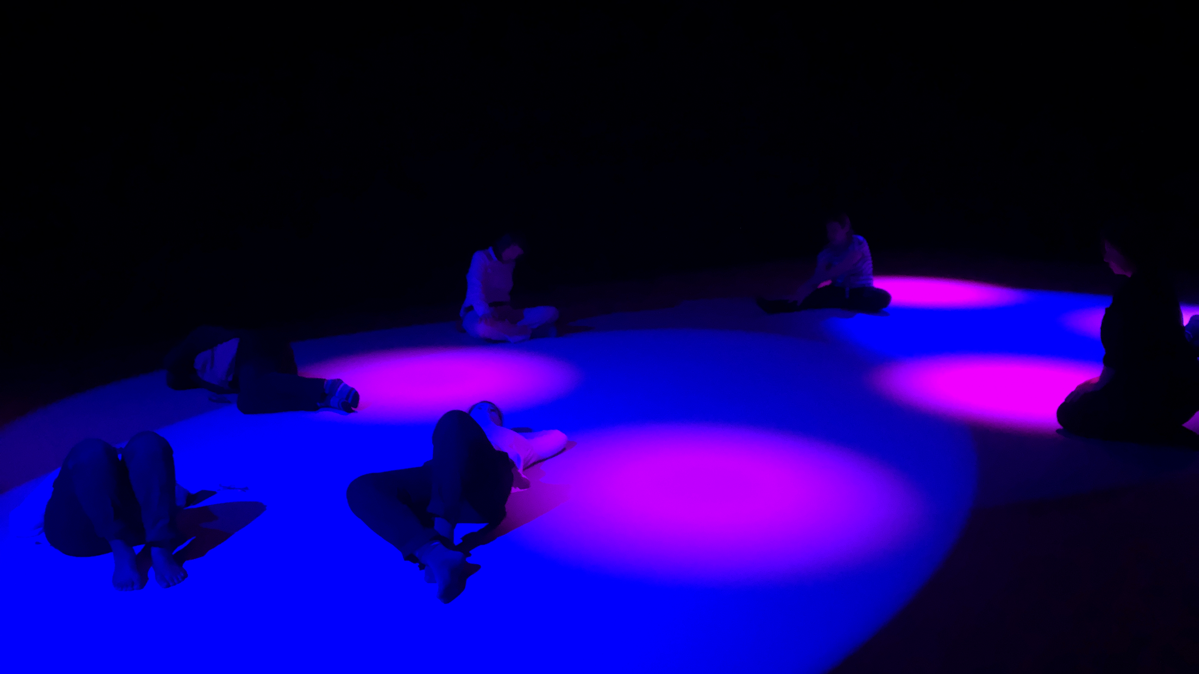 Stillness lab participants lie on the ground immersed in violet light with fuchsia spot lights.