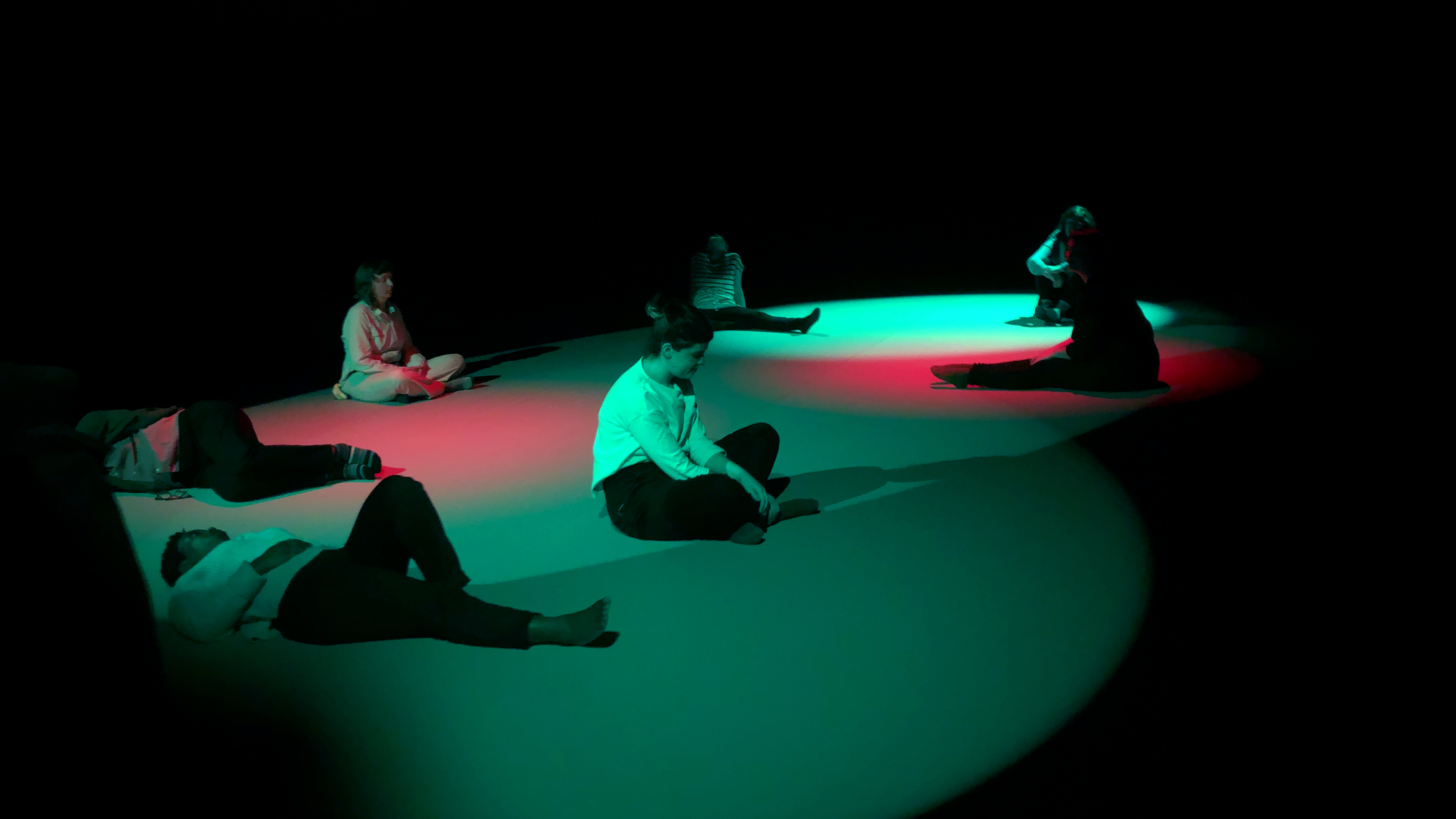 Students and participants sit contemplatively on the floor, which is covered in cyan and red light.