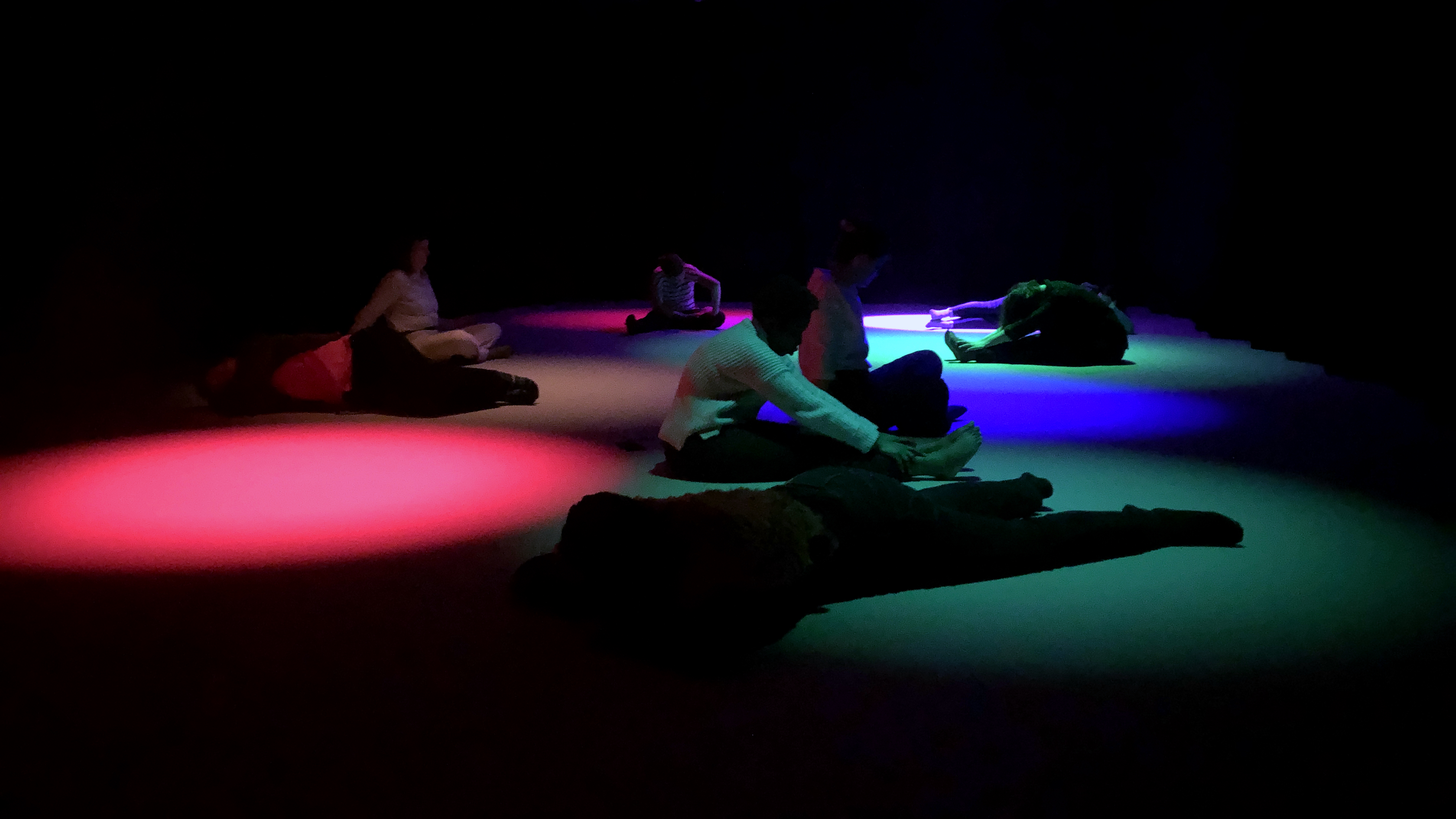 Participants sit on the floor with cyan, red, and blue light covering them and their surroundings.